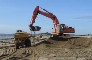Digger loads dumptruck