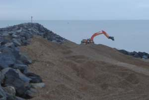 Recovery of beach material by digger from behind the rock spur on the western side of the harbour arm